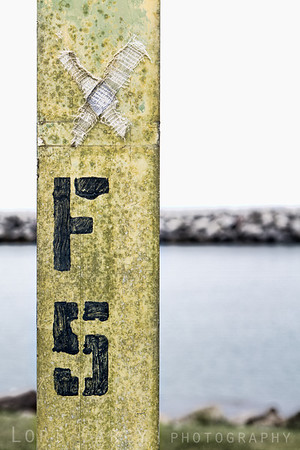 Bandage and grafitti on a sign post at Dana Point Harbor