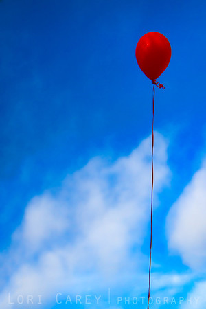 Red balloon against a blue sky with clouds