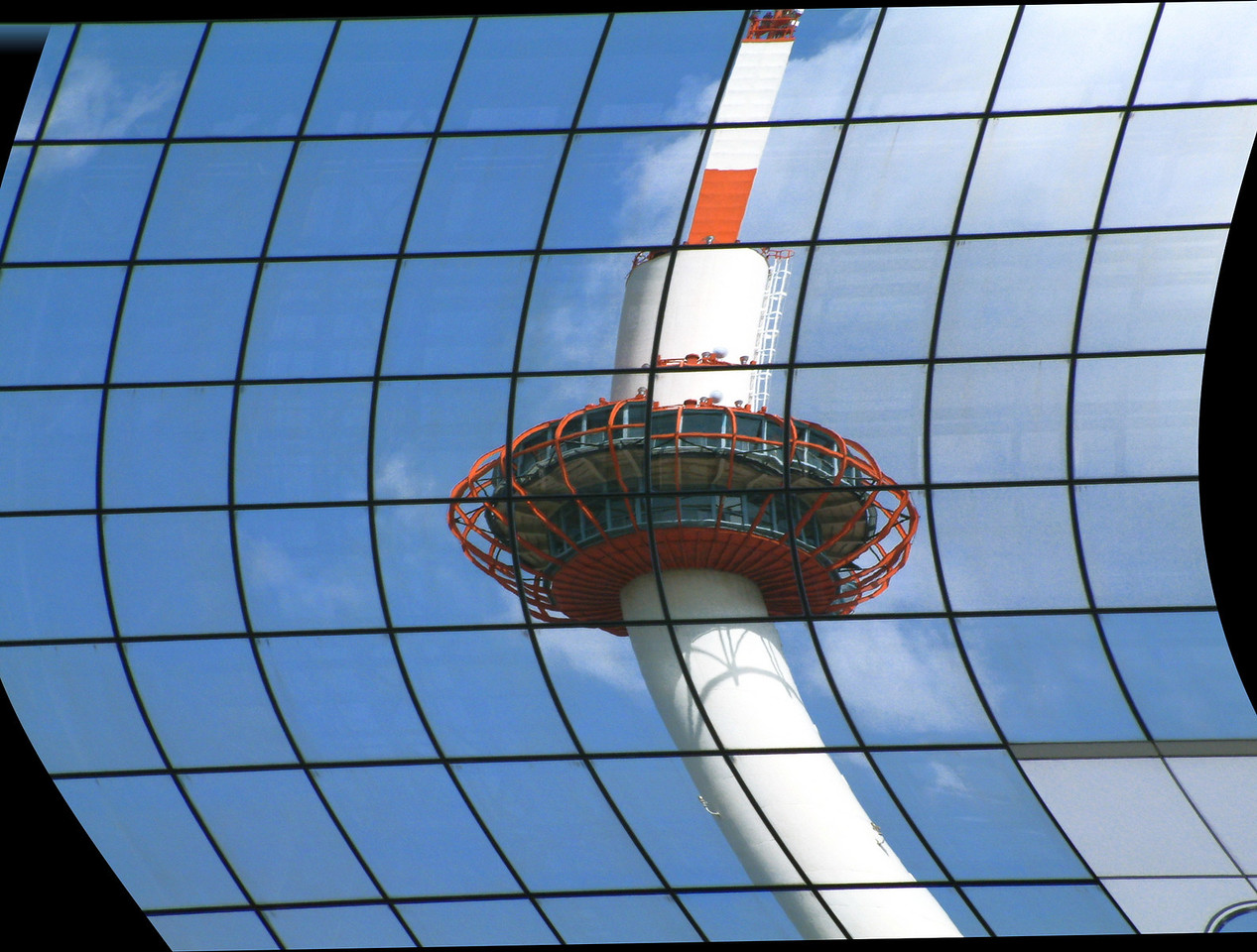 Kyoto Tower reflected in the glass of Kyoto Station.