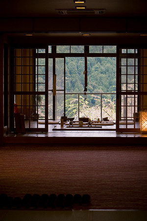 A Japanese Inn with a view over a valley of cherry trees.