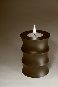 Sepia image of a candle in a wide wooden holder.