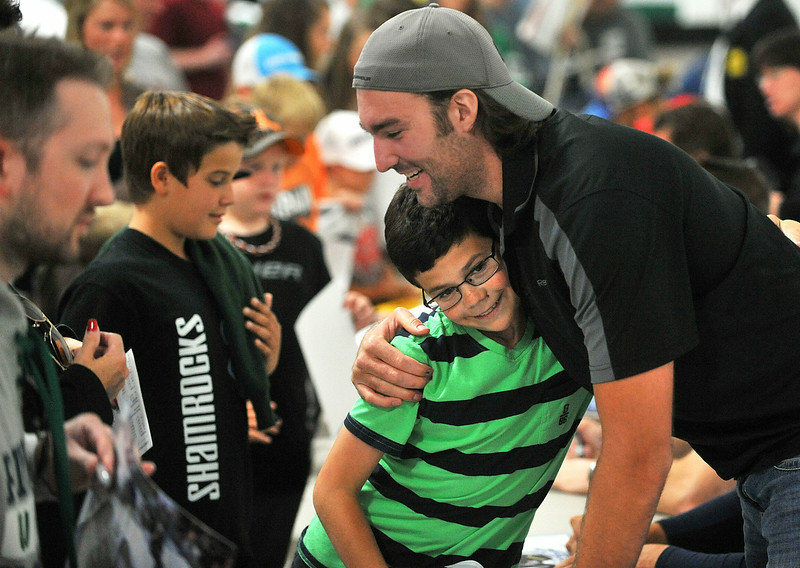 CAPTION INFORMATION Cooper Schummrick of Plymouth gets a hug from former Whaler Mike Yovanic before an Alumni Game at Compuware Arena in Plymouth Twp on Aug 16, 2014.  Cooper's family was a host family for Yovanic when he played for the Whalers.  (Mark Bialek / Special to the Det News)