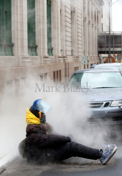 A man sits on a manhole cover as warm steam rises up through it on Shelby Street in downtown Detroit, MI on Oct 29, 2012.  (Photo ©Mark Bialek)