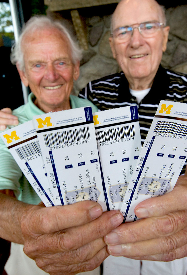 CAPTION INFORMATION Edward Gardner,85, left, and his friend Earl Linford,88, pose with 4 soccer tickets that they were surprised with at Main Street Crossing in Brighton on July 25, 2014.  They will get to see Manchester United play Real Madrid at U-M stadium on August 2.  (Mark Bialek / Special to the Det News)