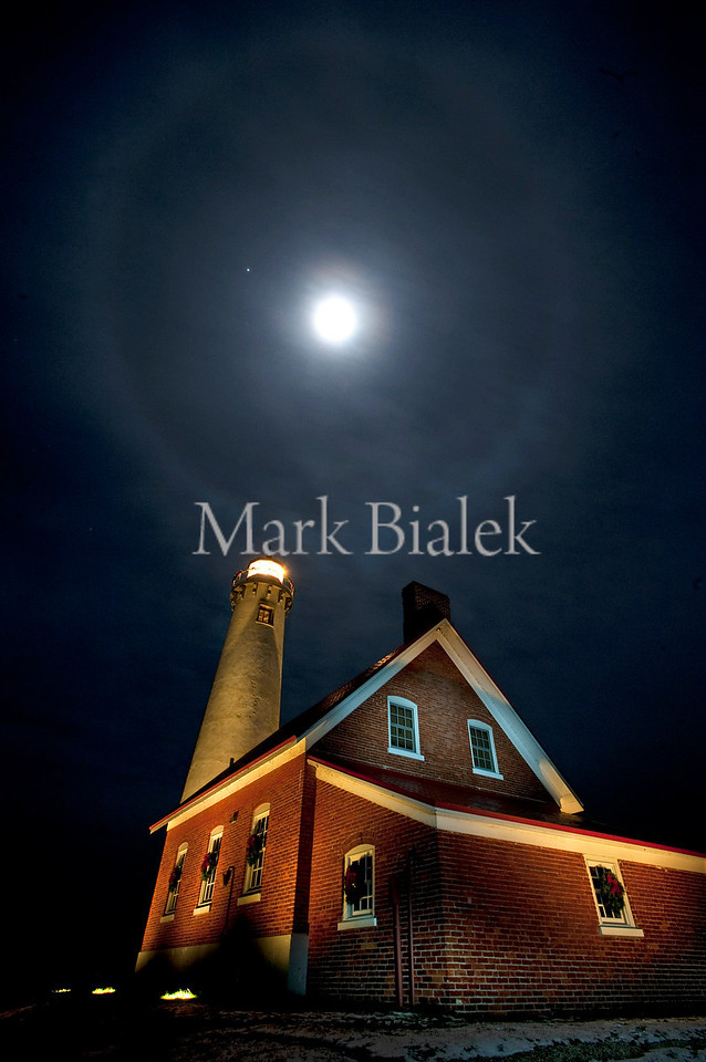 The moon with a halo around it shines through clouds above the lighthouse in Tawas, MI on Nov 27, 2012.