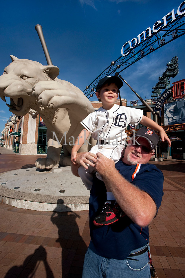 Bob Barron Jr. holds his grandson, Jackson Miller, 4, while posing for pictures in front of Comerica Park in downtown Detroit, MI on Oct 25, 2012.  The Tigers uniform Jackson is wearing is 54 years old.  Work crews around the ballpark are gearing up for this Saturday's World Series game against the Giants in Detroit.