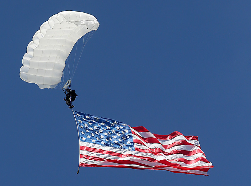 A parachutist displays the American flag during Memorial Day Services at Woodside Cemetery in Middletown Monday, May 30, 2016.