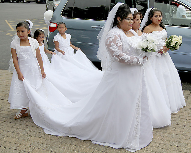 With family members holding their trains, brides Catalina, Hilda, and Rosalinda pose for pictures before entering Saint Ann Catholic Church in Cincinnati for their weddings Sunday, May 21, 2017. (CT Photo/E.L. Hubbard)