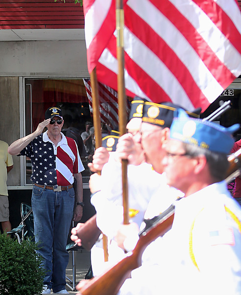 A veteran salutes as an Honor Guard carries the flag past during the Memorial Day parade in Hamilton Monday, May 30, 2016.