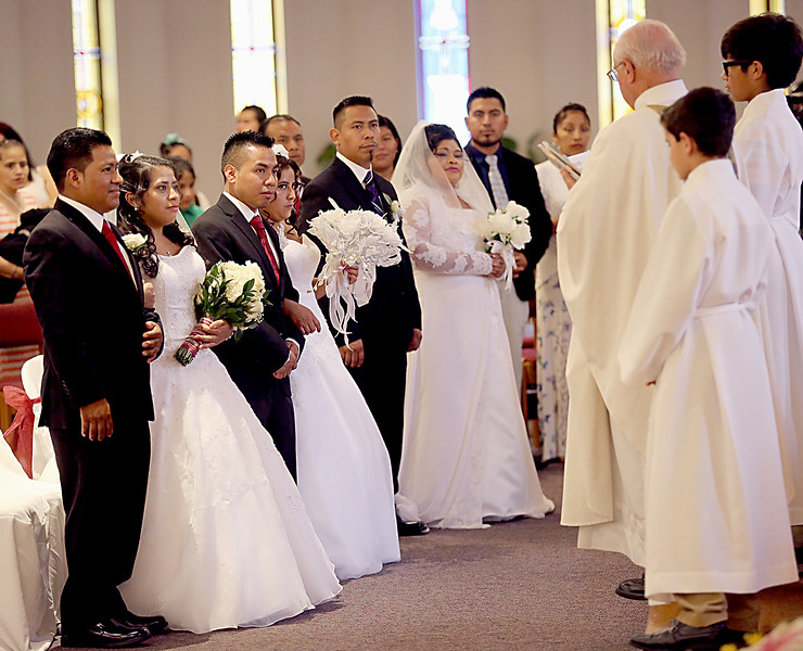 Armando and Rosalinda, Herminio and Hilda, and Catalina and Ramiro prepare to take their wedding vows from Rev. Tom Snodgrass at Saint Ann Catholic Church in Cincinnati Sunday, May 21, 2017. (CT Photo/E.L. Hubbard)