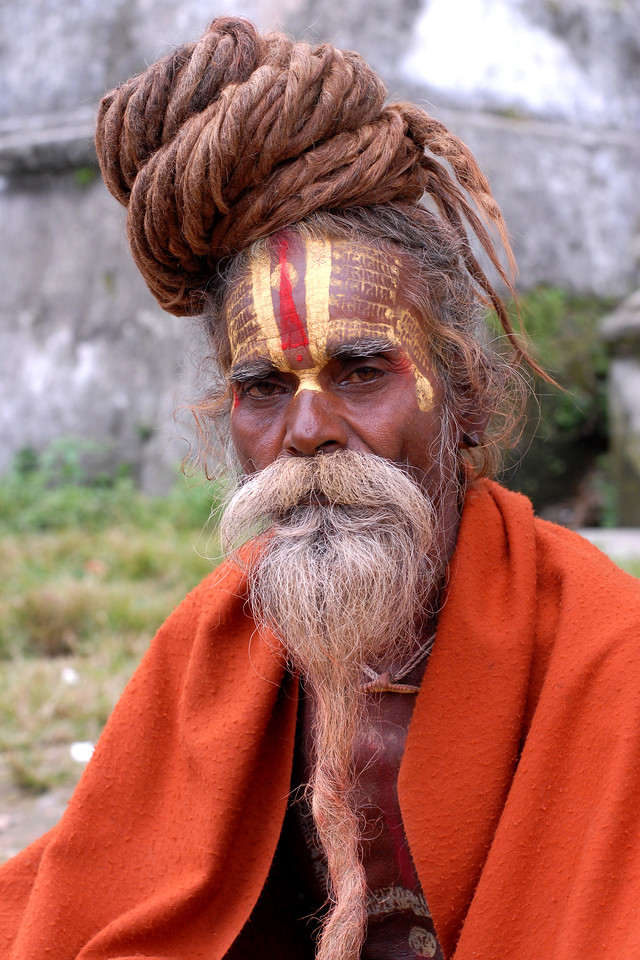 Sadhu (medicant) with his orange robe near Pashupatinath Mandir, Kathmandu, Nepal. These sadhus sit at the temple gates and ask for offerings from devotees. Not all of them are true seekers and some are just dressed up to collect money from innocent people.
