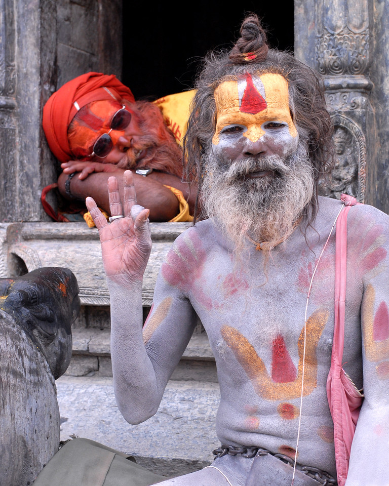 "Ash and colour smeared Sadhu (medicant) with his ""lota"" (the pot behind) and ""kamandal"" near Pashupatinath Mandir, Kathmandu, Nepal. These sadhus sit at the temple gates. Seen behind is another sadhu lying down."
