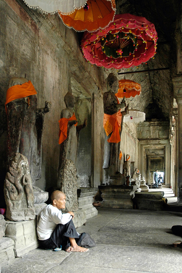 Old lady sitting in Angkor Wat Temple, Siem Reap, Cambodia. Asia. Seen in the image are tall Buddha statues in various conditions.