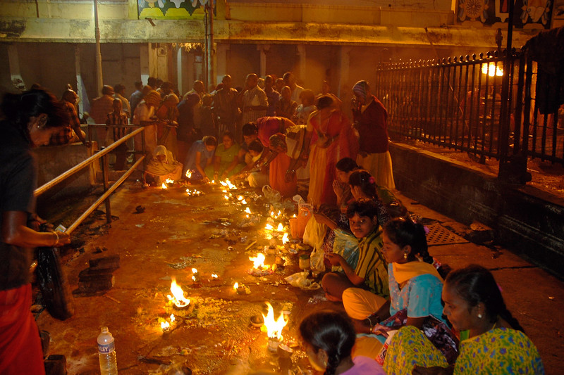 Devotees light oil lamp and offer prayers at Sri Venkateswara Temple in the evening. Tirumala Tirupati dev sthanam.  The ancient and sacred temple of Sri Venkateswara is located on the seventh peak, Venkatachala (Venkata Hill) of the Tirupati Hill, and lies on the southern banks of Sri Swami Pushkarini. <br /> It is by the Lord's presidency over Venkatachala, that He has received the appellation, Venkateswara (Lord of the Venkata Hill). He is also called the Lord of the Seven Hills.<br /> <br /> The temple has its origins in Vaishnavism, an ancient sect which advocates the principles of equality and love, and prohibits animal sacrifice.<br /> <br /> The sanctum sanctorum which houses the awe-inspiring idol of the Lord of the Seven Hills is situated in the main temple complex of Tirumala.