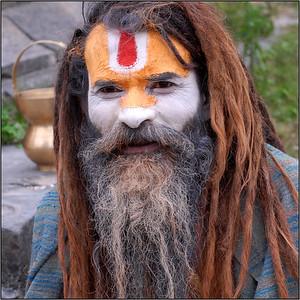 "Ash and colour smeared Sadhu (medicant) with his ""lota"" (the pot behind) and ""kamandal"" near Pashupatinath Mandir, Kathmandu, Nepal."