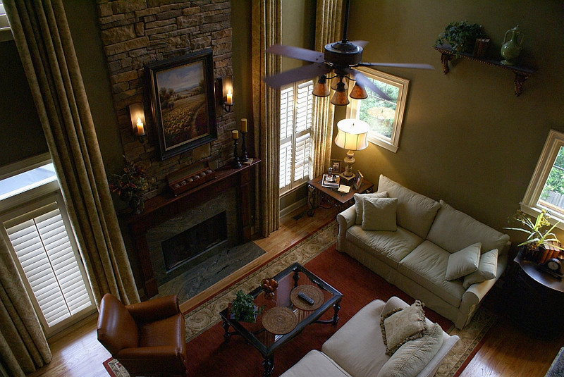 "Living Room: <br /> <br /> Original room felt tall and narrow as if ""Sitting at the bottom of a milk carton.""<br /> <br /> The lower windows at right wall were added for more light and to open up lower half of room.  <br /> The original cultured stone at the fireplace surround and raised hearth were removed.<br /> Adding a wood mantle with granite surround and matching flush to floor hearth created interest to lower half of room also opening up a bit more floor space by eliminating the raised hearth obstruction."