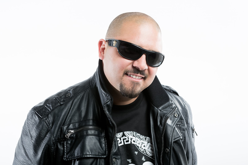 Studio portrait photography of DJ on white backdrop.