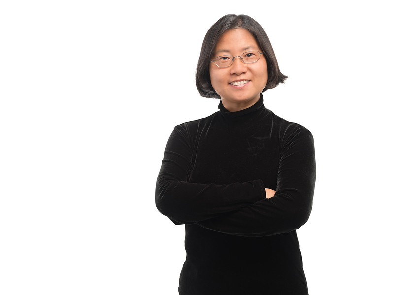 Portrait photography of female CEO in studio against white backdrop.