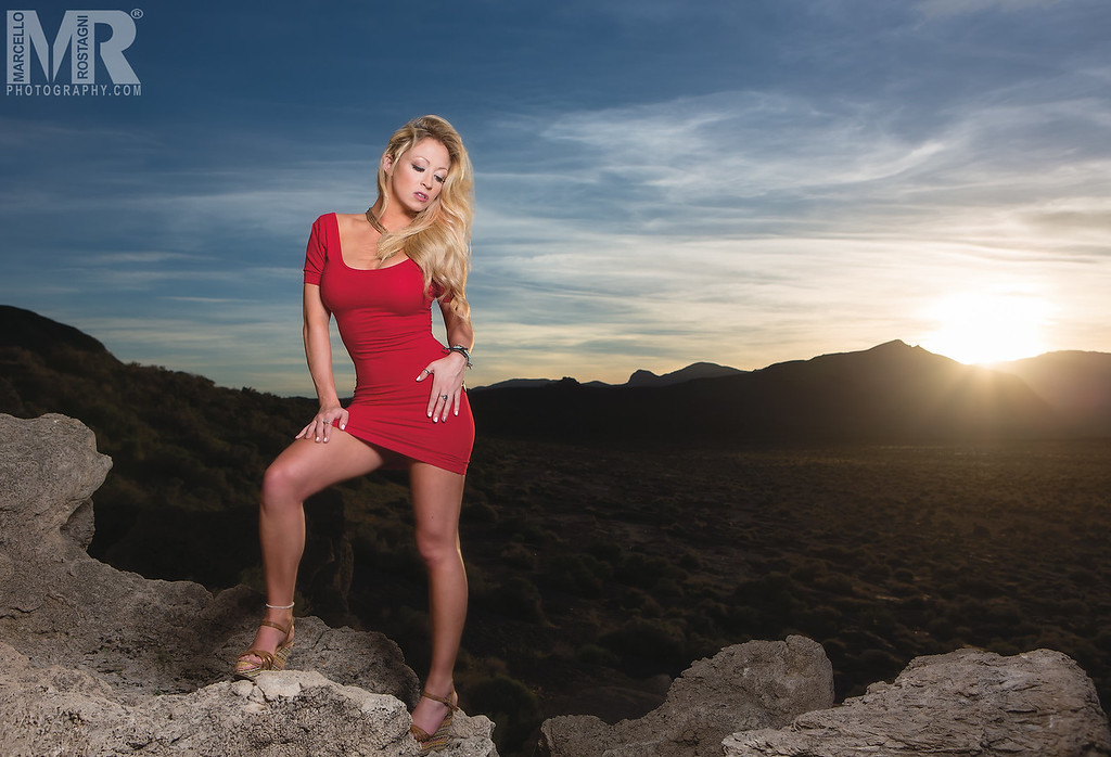 Reno Photographer Marcello Rostagni photographs a model in front of the setting sun in a red dress in Reno, NV.