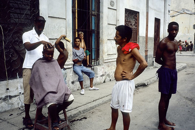 Cutting hair in a street of Cerro quarter.