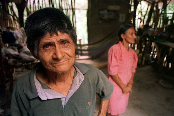 "Benedicto Espinal (L) and his wife Agustina stand in their small home in the village of Concepcion, in southern Honduras August 13, 2001. The Espinals have no food in the house and depend on family and neighbors to get by. Although a food for work program is being offered, Benedicto decides that losing a second crop by working instead of planting corn can only make things worse. ""The only cure is the rain, but what will we eat until the next harvest?"" Agustina asks. REUTERS/Adam Bernstein"