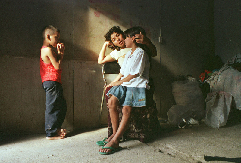 Marta Luz Vargas Sanches (R) sits with two of her four children in their small unit in the Trebol temporary shelter in Tegucigalpa, Honduras October 24, 2001. Marta and her children, along with over 600 other families, have lived in the shelter since losing their homes three years ago during Hurricane Mitch.REUTERS/Adam Bernstein