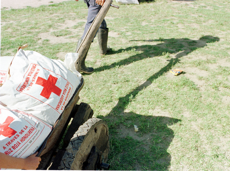 An unidentified farmer hauls bags of seeds and fertilizer in a homemade wheel barrel in the small community of Los Terrones in eastern Honduras September 13, 2001. The American, Dutch and Honduran Red Cross have donated both food and seeds to 15,000 drought affected families in the Central Amrican country. With 300,000 people suffering from effects of  the drought, Honduras is the most widely affected country in th region.  REUTERS,/ Adam Bernstein
