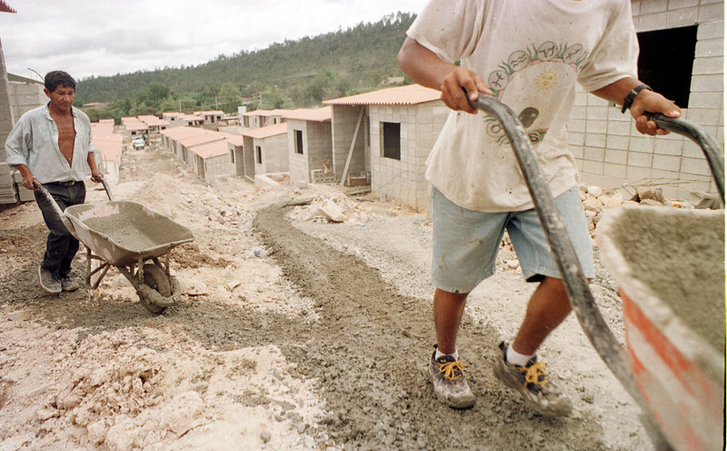 "Thousands of bags of concrete are mixed and hauled by hand in the constrcution of ""Ciudad Espana"" 30 miles outside the Honduran capital of Tegucigalpa, August 30, 2001. The construction project that began in January 2000, will benefit 1,500 families who still live in temporary shelters three years after Huricane Mitch destroyed their homes. The October 1998 Hurricane left as many as 85,000 families homeless in the Central American nation.  REUTERS,/ Adam Bernstein"