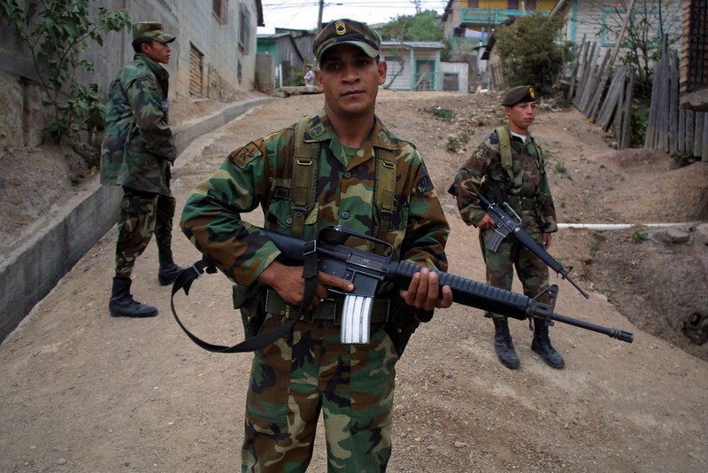 "Honduran soldiers patroling the impoverished Campo Cielo neighborhood in Tegucigalpa, Honduras, March 5, 2002. Nearly 4000 soldiers and police are patroling  the steets of Tegucigalpa and three other Honduran cities in an effort by newly elected president Ricardo Maduro to cut back on soaring crime rates in the Central American country. The new ""zero tolerance"" policy has reduced violent crime by more than 70% but critics wonder how long the government can support the extra costs of the patrols.   REUTERS/ Adam Bernstein."