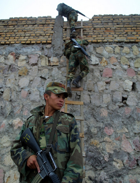"Honduran soldiers climb a ladder while patroling the impoverished Campo Cielo neighborhood in Tegucigalpa, Honduras, March 5, 2002. Nearly 4000 soldiers and police are patroling  the steets of Tegucigalpa and three other Honduran cities in an effort by newly elected president Ricardo Maduro to cut back on soaring crime rates in the Central American country. The new ""zero tolerance"" policy has reduced violent crime by more than 70% but critics wonder how long the government can support the extra costs of the patrols.  REUTERS/ Adam Bernstein."