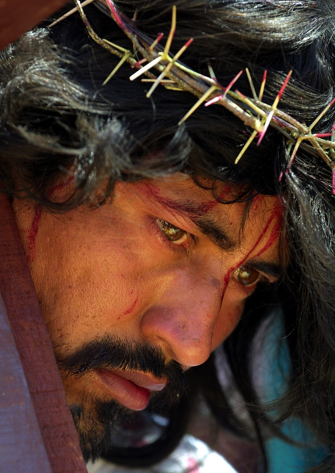 A Honduran man playing the role of Jesus carries his cross to a crucifixion site in a Holy Week reenactment in the San Francisco neighborhood of Tegucigalpa, Honduras, March 29, 2002. Catholics throughout Latin America celebrate Holy Week. REUTERS/Adam Bernstein