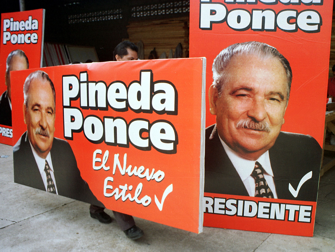 A campaign workers carries a political poster of Liberal party presidental candidate Pineda Ponce September 26, 2001 in Tegucigalpa Honduras. Ponce will be going up against National party candidate Ricardo Maduro in the November 25th election. REUTERS,/ Adam Bernstein