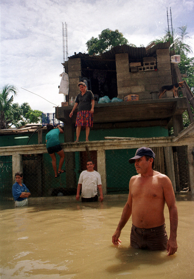 Jose Flores and his family stand outside their home in La Lima, Honduras, October 2, 2001. Flood waters are slowly receding in La Lima, one of the worst hit communities affected by the four-day tropical storm that left 25,000 temporarily homeless throughout northern Honduras. REUTERS/Adam Bernstein