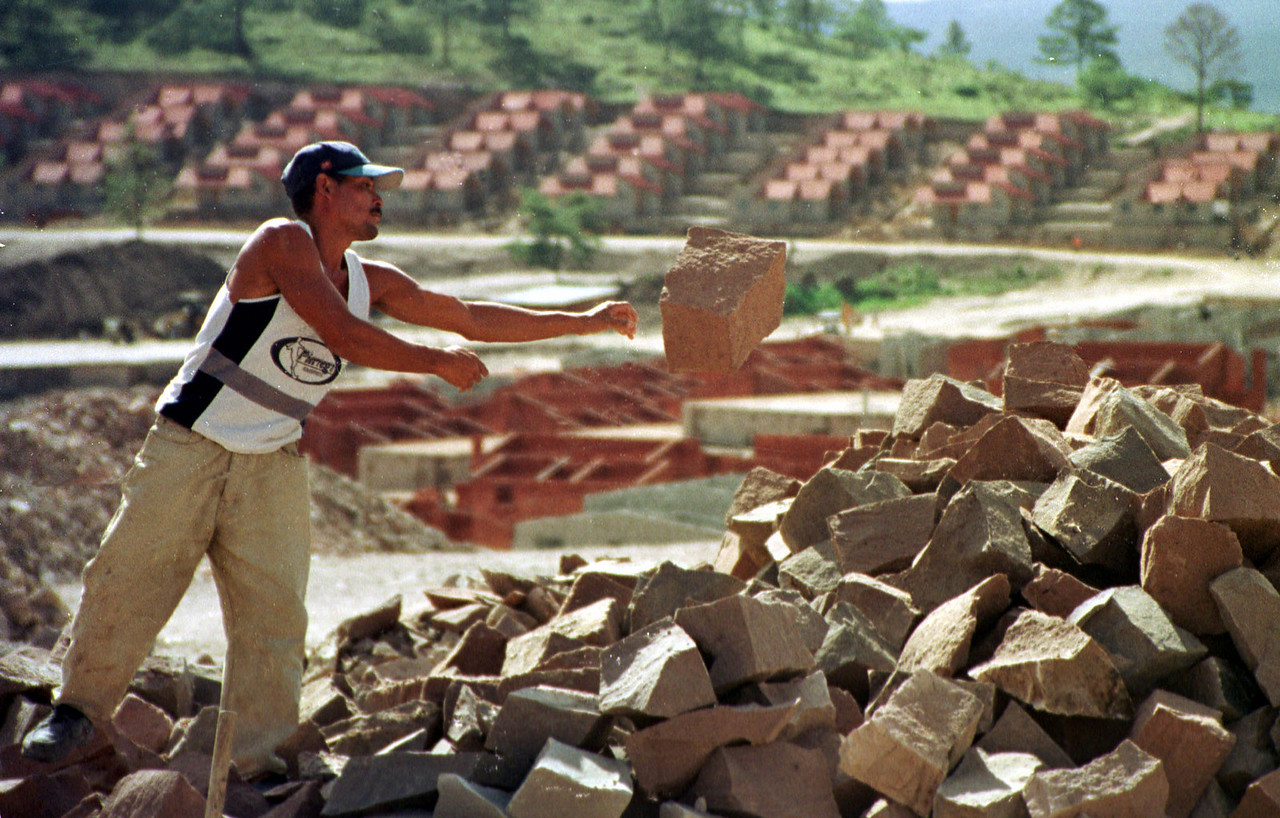 "One of 1,500 beneficiares of the ""Ciudad Espana"" housing project throws hand cut stones that will be used in the construction of new residences, August 30, 2001 outside Tegucigalpa, Honduras. The Spanish and Swiss Red Cross are the principal contributors for one of the last housing projects for families who lost their homes nearly three years ago in the biggest natural disater in Honduran history. The October 1998 Hurricane left as many as 85,000 families homeless in the Central American nation.  REUTERS,/ Adam Bernstein"