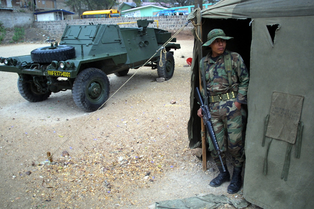 "A Honduran soldier stands outside temporary barracks in the impoverished Campo Cielo neighborhood in Tegucigalpa, Honduras, March 5, 2002. Nearly 4000 soldiers and police are patroling  the steets of Tegucigalpa and three other Honduran cities in an effort by newly elected president Ricardo Maduro to cut back on soaring crime rates in the Central American country. The new ""zero tolerance"" policy has reduced violent crime by more than 70% but critics wonder how long the government can support the extra costs of the patrols.  REUTERS/ Adam Bernstein."
