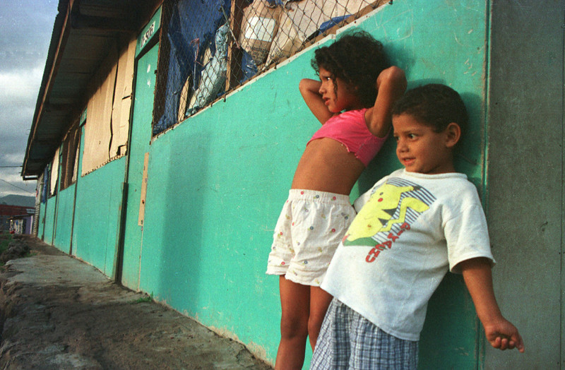 Adelina Sanchez (L) and her little brother Luis watch the sun rise over the capital from outside their unit in the Trebol temporary housing shelter in Tegucigalpa, Honduras October 26, 2001. Thousands of children live in the shelter as their parents fight to move them on to new homes and a better future. The shelter was built three years ago after Hurricane Mitch ravaged this Central American nation leaving nearly six thousand dead and 35,000 homeless. Today, the shelter which was expected to last no more than one year, is still home to over 600 families. REUTERS/Adam Bernstein