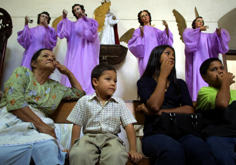 Honduran catholics sit in front of statues of angles before an evening mass at the National Cathedral in Tegucigalpa, Honduras, March 28, 2002. Catholics throughout Latin America celebrate Holy Week with processions and religous festivals. REUTERS/Adam Bernstein