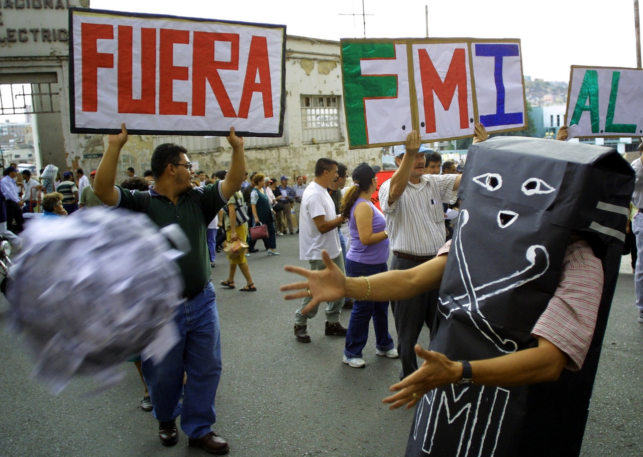 A man dressed as the  tombstone of the International Monetary Fund throws a ball representing wasted money during a protest in Tegucigalpa, Honduras March 14, 2002.  Thousands turned out to demondtrate against privatization, new trade agreements and Honduras' commitment to the IMF.  REUTERS/ Adam Bernstein.