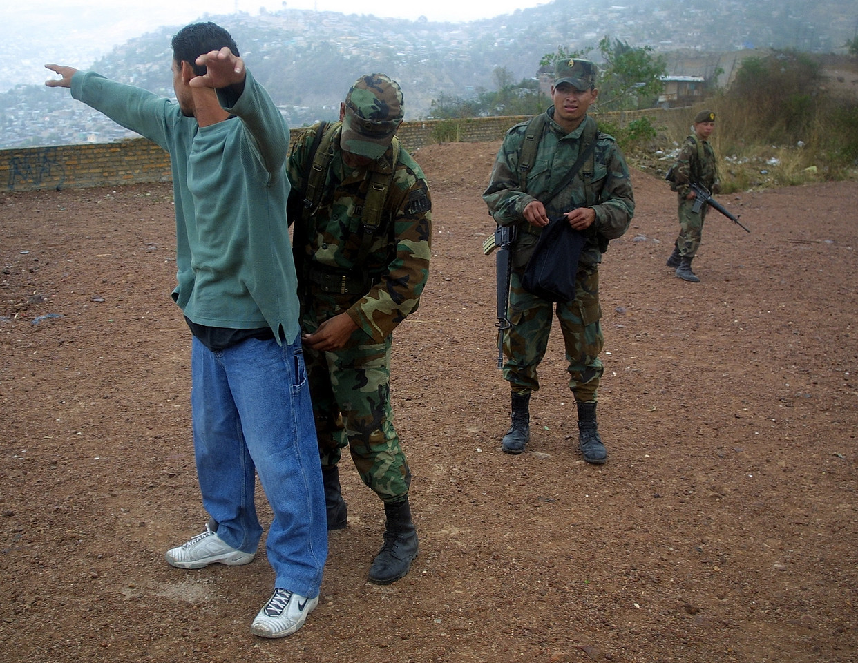 "Honduran soldiers check a citizen for weapons in the impoverished Campo Cielo neighborhood in Tegucigalpa, Honduras, March 5, 2002. Nearly 4000 soldiers and police are patroling  the steets of Tegucigalpa and three other Honduran cities in an effort by newly elected president Ricardo Maduro to cut back on soaring crime rates in the Central American country. The new ""zero tolerance"" policy has reduced violent crime by more than 70% but critics wonder how long the government can support the extra costs of the patrols.  REUTERS/ Adam Bernstein."