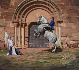 Handsome PRE Stallion Jalisco Garrocha , owned by Mariluz Duende, ridden by Tomas Santiago Solana,  with dancer Mariluz García, in front of the Castle and Monastery at  Escornalbou, Spain