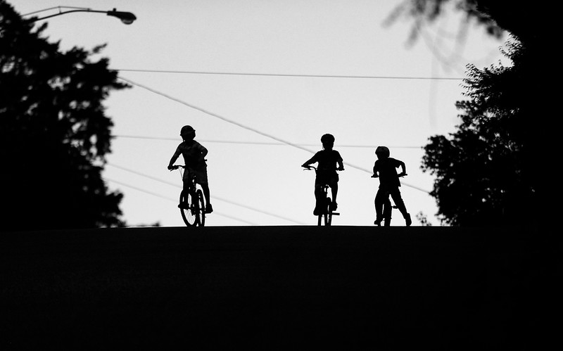 Three boys race down the hill on Wall Street in North Bend, Ore. on Thursday, July 13, 2017.