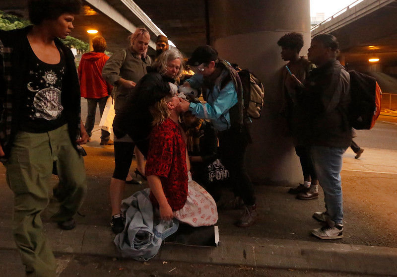Protesters give aid to a man that was hit by pepper spray during a protest in downtown Seattle, WA on July 7, 2016. The protest was a reaction to the killing of Alton Sterling,  37-year-old black man, by two Baton Rouge police officers outside a convenience store in Louisiana in two days earlier.