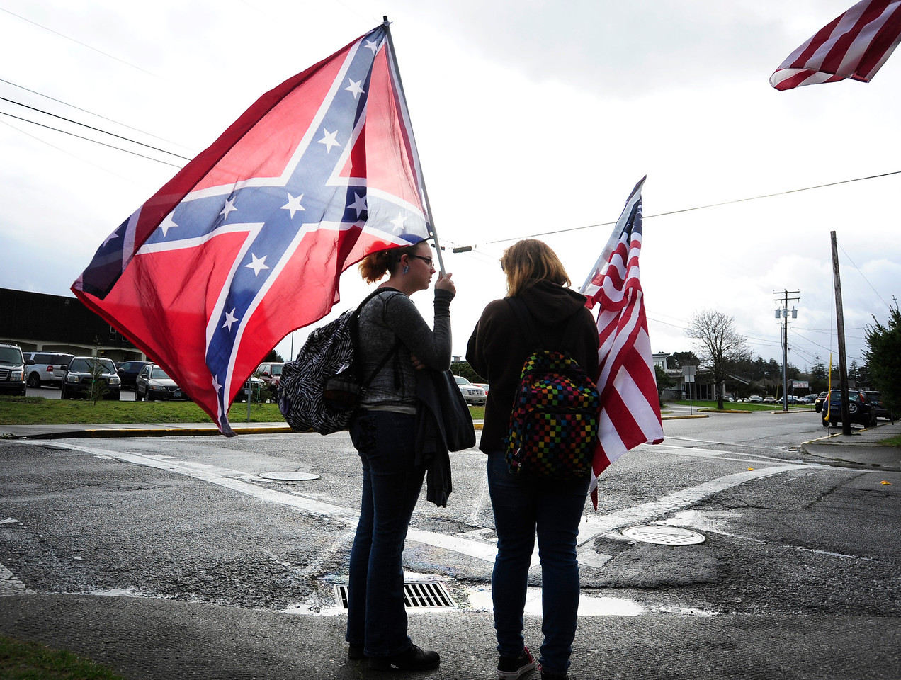 North Bend High School students Dallas Stockton, left, and Autumn Sisson protest outside the high school Monday morning after the district banned the flag widely associated with the slave-holding Confederate States of America.