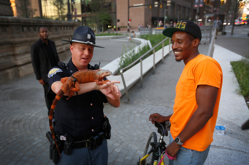 Indiana State Trooper Justin Geltmaker pets a red iguana named 'Fluffy' while Marlow Butts holds her leash in Public Square near the Republican National Convention in Cleveland, Ohio on July 18, 2016.