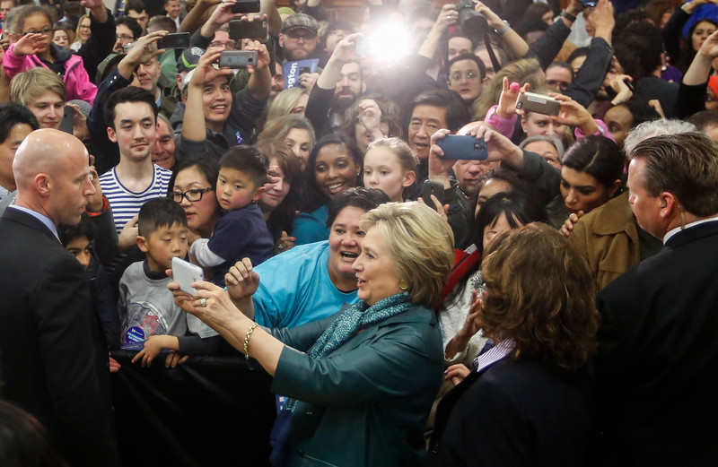 Democratic presidential candidate Hillary Clinton takes a selfie with supporters at Rainier High School after a campaign stop in Seattle, WA on March 22, 2016.