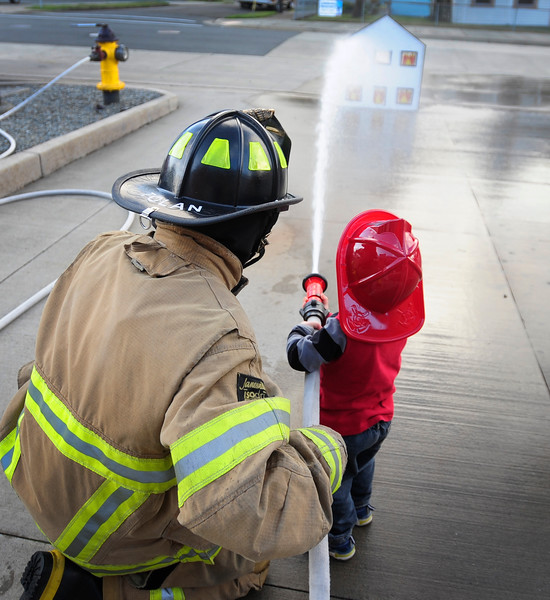 Jasper Krug, 2, of Coos Bay, holds a water hose with a Coos Bay firefighter to simulate extinguishing a house fire during the open house at the Coos Bay Fire Department Station #1 to celebrate Fire Prevention Week in Coos Bay on Wednesday.