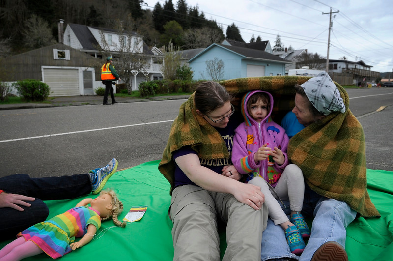 Melanie Mariotti, left, and Janness Delaney, right, speak with Teagen McKinney, 4, as they pretend to be injured in a Community Emergency Response Team (CERT) exercise in Reedsport, Ore. on Saturday, March 25, 2017. Reedsport Fire Department and Lower Umpqua Hospital EMS responded to a scenario involving a motor vehicle accident and a collapsed building caused by an earthquake.