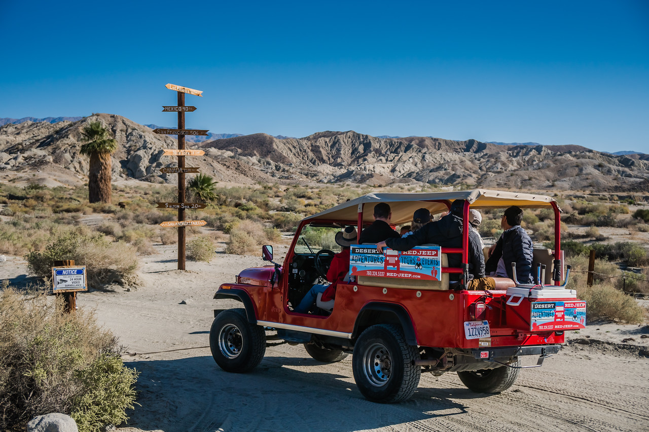 Red Jeep with tourists on a desert road