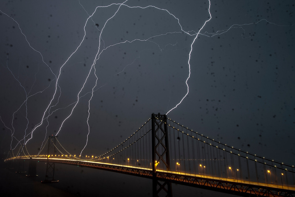 Bay Bridge Lightning Strike  San Francisco, California   This is the photo that started it all.  I would like to think that I occasionally took a good photo before this one (and since) but none have ever garnered the attention that this one has.  It was taken out through the window of my home office.  Lightning is increidby rare in Northern California.  I had often thought that if lightning did strike, some large metal rods surrounded by saltwater would make a great conductor.  I watched the storm approach the city on an app which plots lightning strikes.  I set up my camera as close as I could get to the window and darkened the room.  I set the exposures for 20 seconds and when done, I had take 136 shots.  Three frames had lightning in them.  This one represents the most stirkes.  I cannot state that all stikes hit simutaneously but I can say with certainty that they occurred within 20 seconds of each other.  This photo has appeared on local and national TV as well as numerous print publications.  These include the UK Daily Mail, the NBC Nightly News, and The San Francisco Chronicle.  I was interviewed by the local NBC and CBS affiliates and the interview aired on the local evening broadcasts.