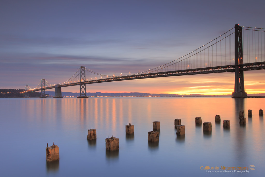 """San Francisco Bay Bridge"" <br>Location: Embarcadero Plaza, San Francisco, California.  <p><p>I shot this image just before the sun came up and lit the whole scene (see next)... that is still my favorite image. However, I liked this image because it has both the warm glow of the twilight and also the magic of the cool blue tones.  <p>Tech Info: <br>Lens: Canon EF 17-40mm f/4L @ 24mm <br>Camera: Canon EOS 5D Mk II <br>Exposure: 30sec at f/13 and ISO 50 <br>Filters: LEE ND Grads 0.9 and 0.6 soft edge <br>Post Processing: Adobe Lightroom for white balance, shadow details, Adobe PS for wide angle lens distortion correction. Rest is straight from the camera."